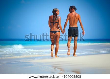 Young couple walking on a sandy beach along a coastline