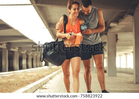 Young couple walking on street in sports wear.They going to gym.
