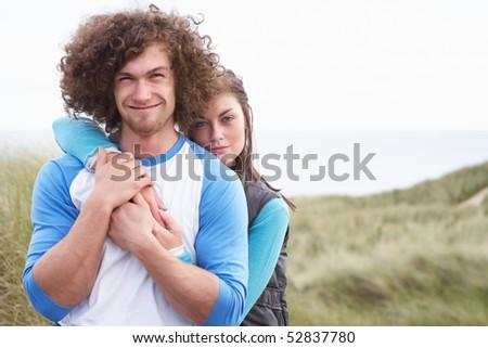 Young Couple Walking Through Sand Dunes Wearing Warm Clothing
