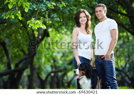Young couple walking with a dog in the park