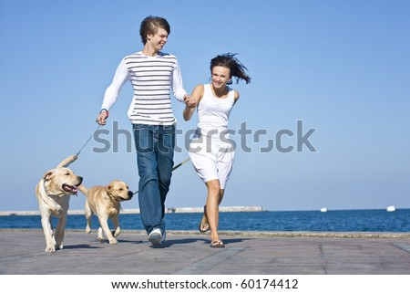 Young Couple Walking with Dogs