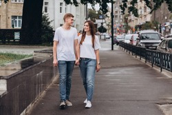 young couple walks the streets of the city and hold hands. guy and girl in white t-shirts and jeans outdoors. Teenagers walk in the autumn city. Happy young couple.