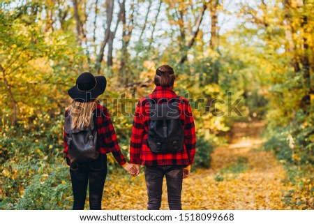 young couple walks through the autumn forest holding hands. Stylishly dressed guy and girl. The guy and the girl in red jackets on background of yellow forest. Happy young couple in love at the park