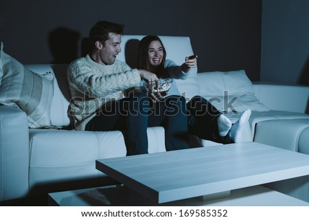 Young couple watching a comedy on TV