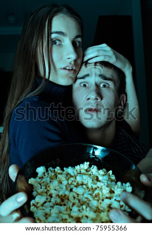Young couple watching scary movie on tv at Halloween