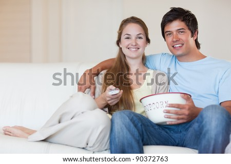 Young couple watching television while eating popcorn in their living room
