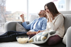 Young couple watching TV on a sofa at home