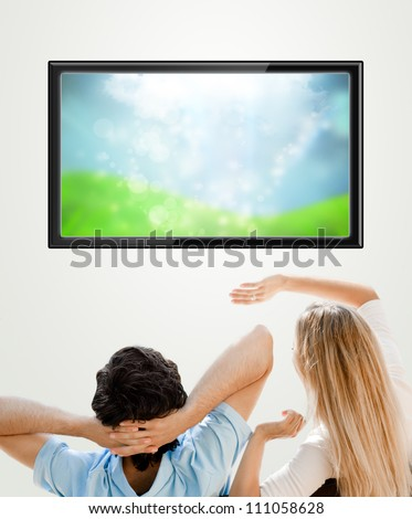 Young couple watching tv. Photo from behind. Lots of copyspace