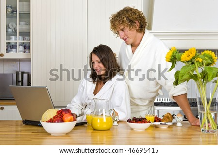 Young couple wearing bath robes enjoying a healthy breakfast in a kitchen behind a laptop