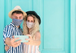 Young couple wearing face mask taking selfie with mobile smartphone on vacation - People having fun traveling again during corona virus outbreak - Love relationship and technology concept