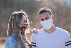Young couple wearing medical mask outdoors. Spring lifestyle 2020. Coronavirus epidemic. Coronavirus spread prevention. People in face mask with positive emotions. Global coronavirus pandemic.