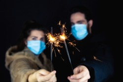 Young couple wearing protective face masks for Coronavirus and holding sparklers for New year's eve, 2021 and Covid-19 concept
