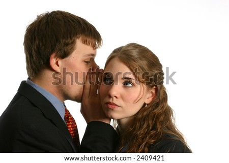Young couple whispering secrets in workplace