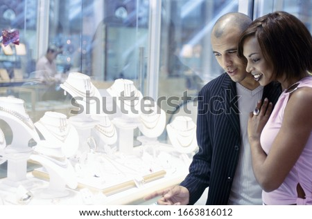 Young couple window-shopping for jewellery together, side view