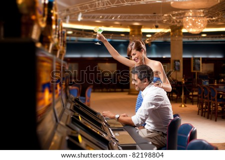 young couple winning at slot machine - stock photo