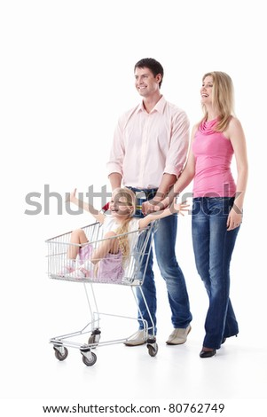 Young couple with a child with a trolley for shopping isolated