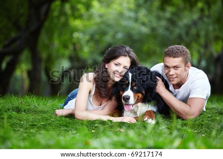 Young couple with a dog in the park - stock photo