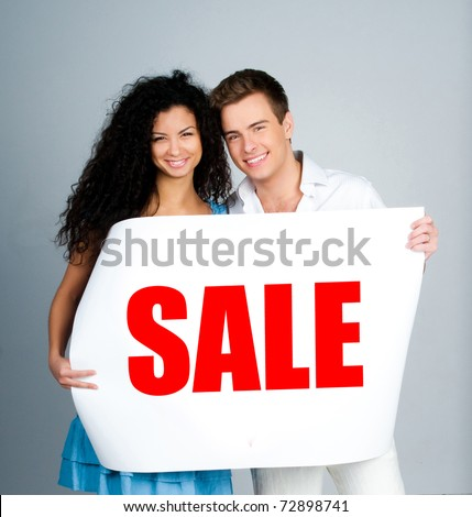 "young couple with a placard ""sale"" on a lihgt"