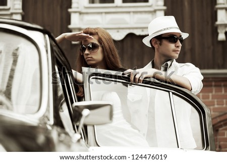 Young couple with a retro car in conflict