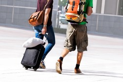 Young couple with a travel bag. Urban scene.