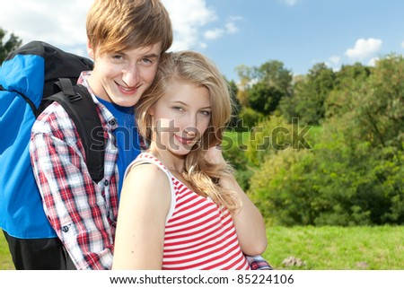 young couple with backpack, hugging and smiling