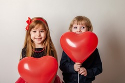 young couple with balloons with hearts in their hands. Romantic, festive mood. A boy and a girl in red
