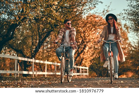Young couple with bicycles in park in autumn time.