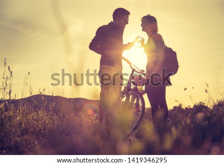 Young couple with bike are standing on a field and doing a gesture, sundown scenery #1419346295