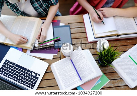Young couple with books and notes in cafe. Smart young guy and girl in University campus. Learning and education for young people. Top view of students studying or doing homework