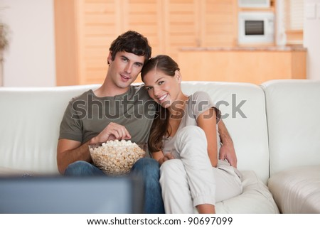 Young couple with bowl on popcorn watching a movie on the sofa