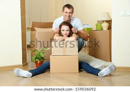 Young couple with boxes in new home on room background