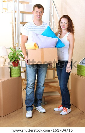 Young couple with boxes in new home on staircase background