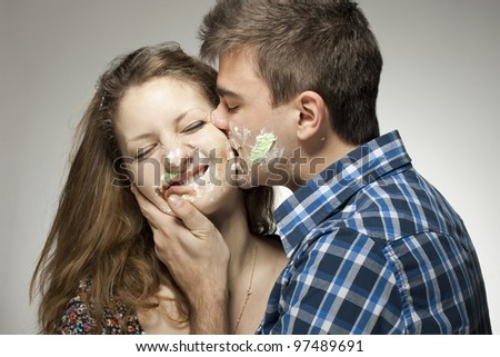 Young couple with cake on face.