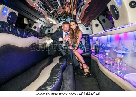 Young Couple With Champagne Flutes In Limousine