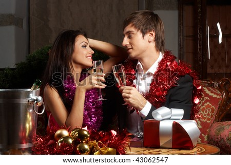 Young couple with champagne glasses celebrating christmas