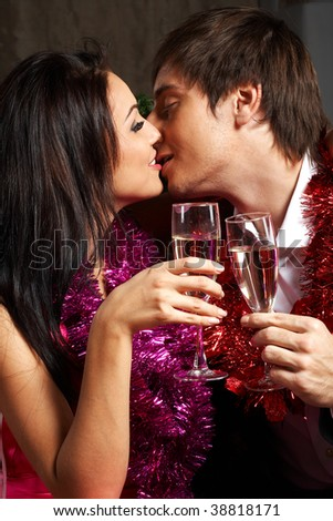 Young couple with champagne glasses kissing - stock photo