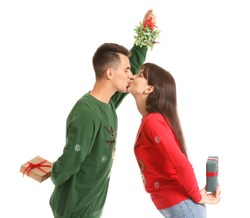 Young couple with Christmas gifts kissing under mistletoe branch on white background