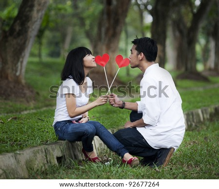 Young couple with cutout of red heart in the nature - stock photo
