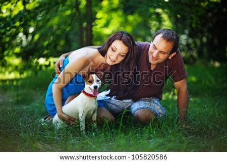 Young couple with dog on picnic in park