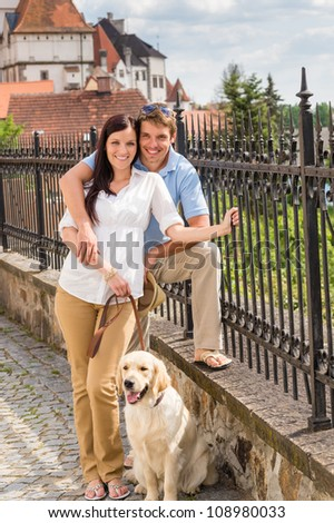 Young couple with dog posing at historical town sunny day