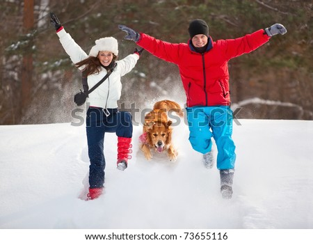 Young couple with dog winter outdoors fun.