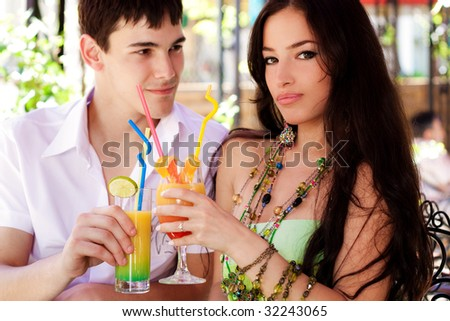 young couple with drinks in cafe outdoor, summer day
