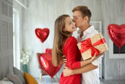 Young couple with gift box hugging at home