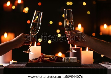 Young couple with glasses of champagne having romantic candlelight dinner at table, closeup