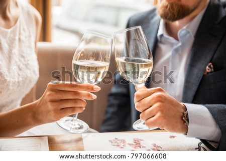 Young couple with glasses of white wine on a date in a cozy Italian restaurant. Leisure, drinks, people and holidays concept - happy man and woman clinking glasses. #797066608