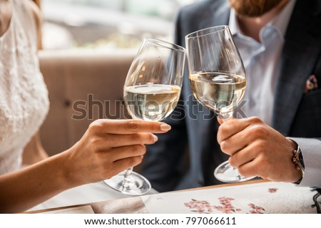 Young couple with glasses of white wine on a date in a cozy Italian restaurant. Leisure, drinks, people and holidays concept - happy man and woman clinking glasses.
