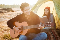 Young couple with guitar in tent. so happy couple. singing songs