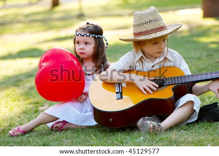 Young couple with guitar on grass in park