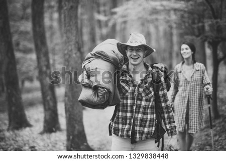 Young couple with happy faces walks. Man with woman hiking with overnight stay or picnic. Couple in love hiking in forest with touristic equipment, trees on background, defocused. Tourists concept.