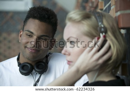 young couple with headphones listening to music